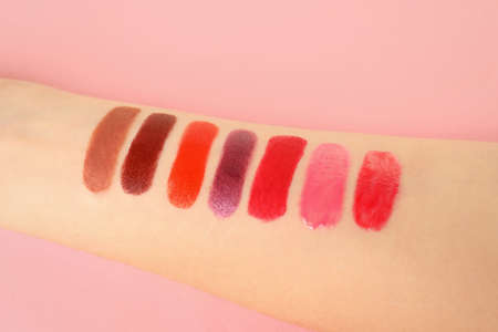 Woman with lipstick swatches on color background, closeup