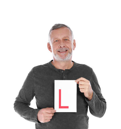 Happy mature man with L-plate on white background. Getting driving license