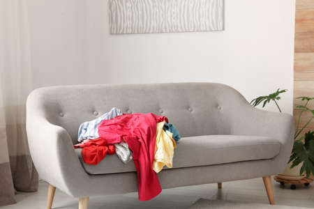 Pile of clothes on sofa in dressing room. Renew wardrobe Foto de archivo - 115560864
