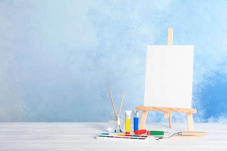 Caballete de madera con tablero de lienzo en blanco y herramientas de pintura para niños en la mesa junto a la pared de color. Espacio para texto