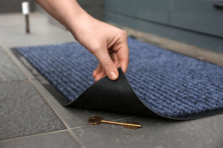 Woman's hand lifting door mat to reveal key hidden underneath, closeup