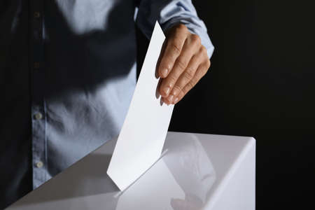 Man putting his vote into ballot box on black background, closeup