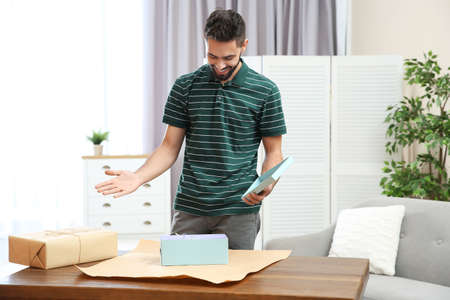 Young man opening parcel on table at home