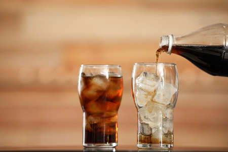 Pouring cola from bottle into glass with ice cubes on table against blurred background Фото со стока