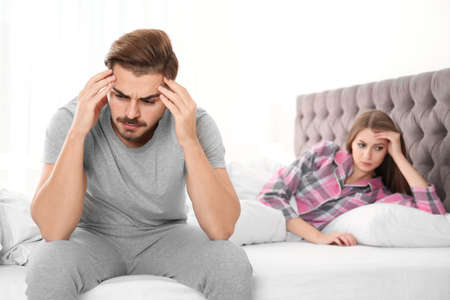 Young couple with relationship problems ignoring each other in bedroom