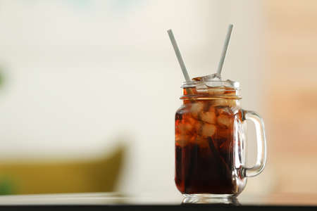 Mason jar of cola with ice on table against blurred background. Space for text Stockfoto