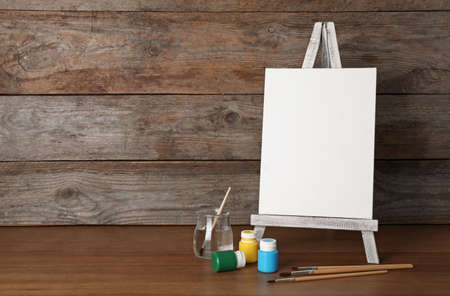 Easel with blank canvas board and painting tools for children on table near wooden wall. Space for text