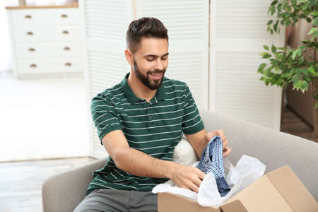 Young man opening parcel on sofa at home Stock Photo
