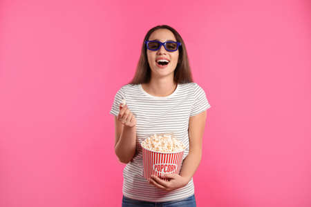 Woman with 3D glasses and popcorn during cinema show on color background