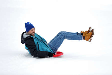 Man sliding on sled outdoors. Winter vacation