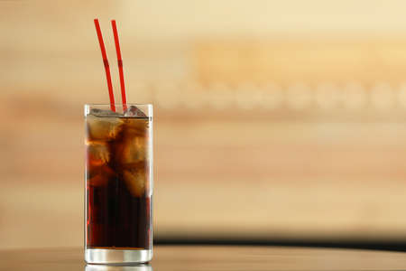 Glass of cola with ice on table against blurred background. Space for text Фото со стока