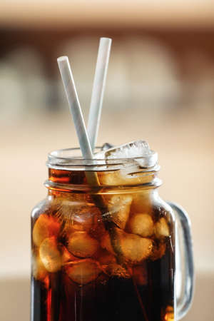 Mason jar of cola with ice against blurred background