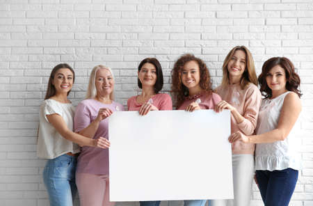 Women wearing silk ribbons holding poster with space for text against brick wall. Breast cancer awareness concept Imagens - 115789245