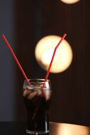 Glass of cola with ice on table against blurred background