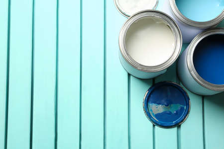 Colorful paint cans on blue wooden background, top view. Space for text