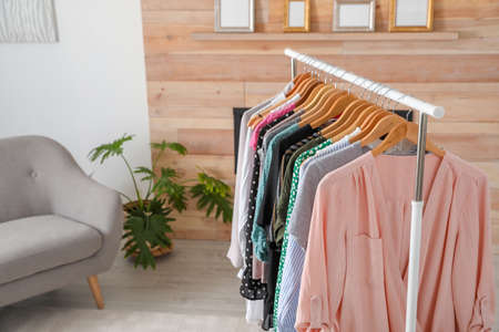 Wardrobe rack with stylish clothes and sofa in dressing room. Space for text Stockfoto