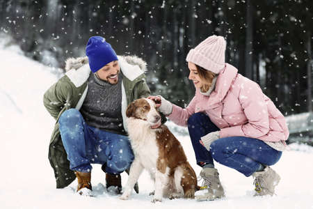 Cute couple with dog outdoors. Winter vacation