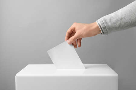 Man putting his vote into ballot box on light background, closeup