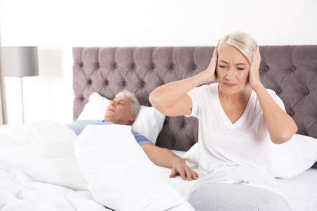 Upset mature woman sitting on bed near her sleeping husband at home. Relationship problems 写真素材