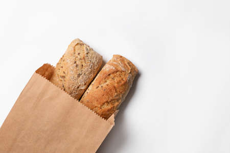 Paper bag with bread loaves on white background, top view. Space for text