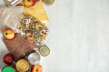 Many different products and space for text on white wooden background, flat lay. Food donation