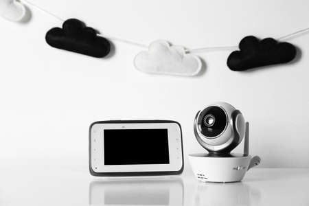 Modern CCTV security camera, monitor and nursery garland on background. Space for text