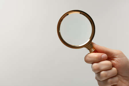 Woman holding magnifying glass on white background, closeup. Space for text Stock Photo