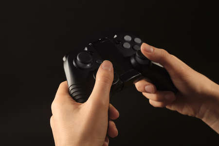 Woman holding video game controller on black background, closeup