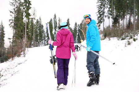 Couple of skiers on slope at resort. Winter vacation