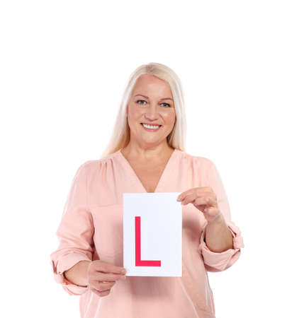Happy mature woman with L-plate on white background. Getting driving license Reklamní fotografie