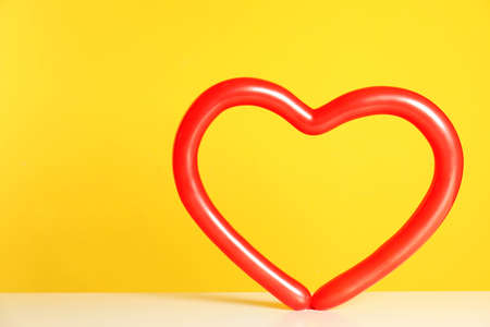 Heart figure made of modelling balloon on table against color background. Space for text