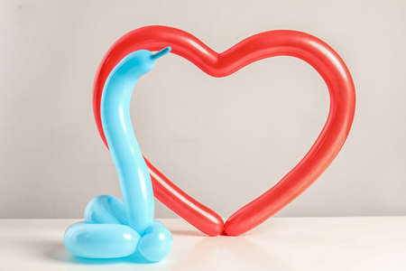 Snake and heart figures made of modelling balloons on table color light background
