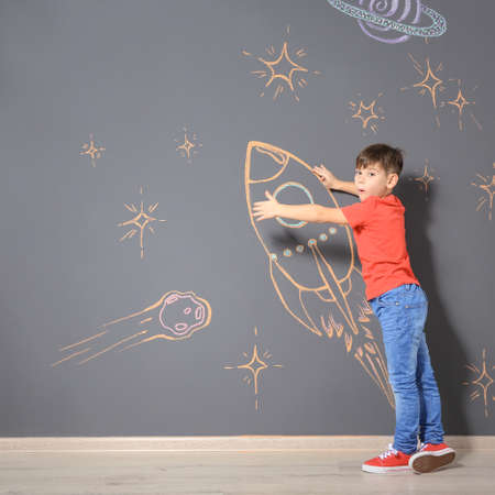 Cute little child playing with chalk rocket drawing on grey wall