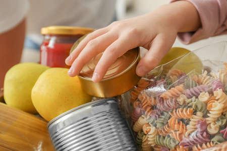 Girl taking food out of donation box, closeup Фото со стока