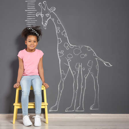 African-American child near grey wall with chalk giraffe drawing and height meter Foto de archivo - 115790155