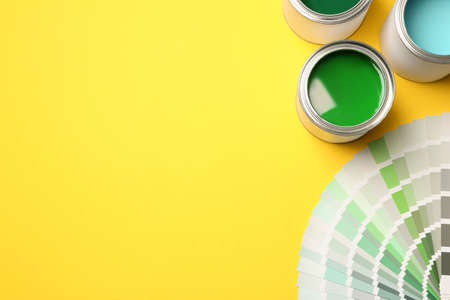 Paint cans and color palette on yellow background, top view. Space for text 免版税图像