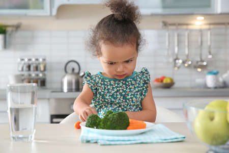 Cute African-American girl with plate of vegetables at table in kitchen Banco de Imagens