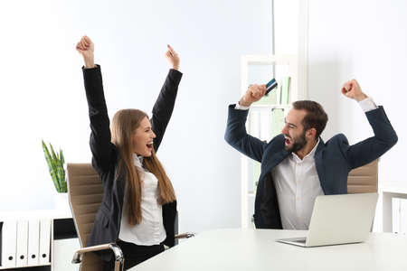 Emotional young people with credit card and laptop celebrating victory in office Archivio Fotografico