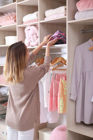 Woman taking pajamas from wardrobe shelf Banco de Imagens