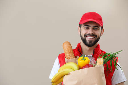 Man holding paper bag with fresh products on color background, space for text. Food delivery service Imagens