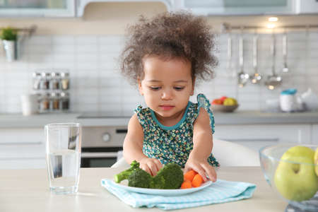 Nettes afroamerikanisches Mädchen, das Gemüse am Tisch in der Küche isst Standard-Bild