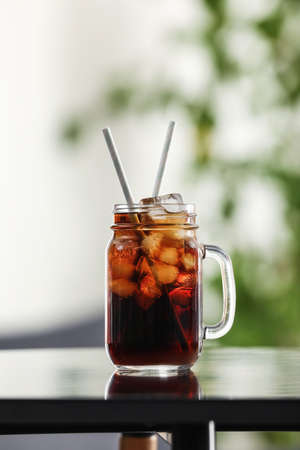 Mason jar of cola with ice on table against blurred background Archivio Fotografico