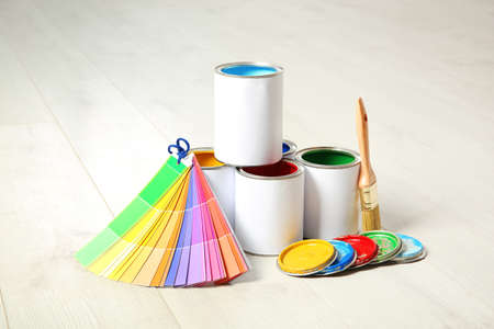 Cans of paint, brush and color palette on wooden floor indoors Reklamní fotografie