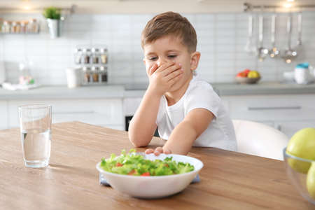 Little boy covering his mouth and refusing to eat vegetable salad at table in kitchen Stock Photo