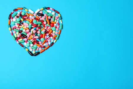 Heart made of pills on color background, top view. Space for text