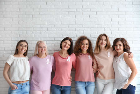 Group of women with silk ribbons near brick wall. Breast cancer awareness concept Stock Photo