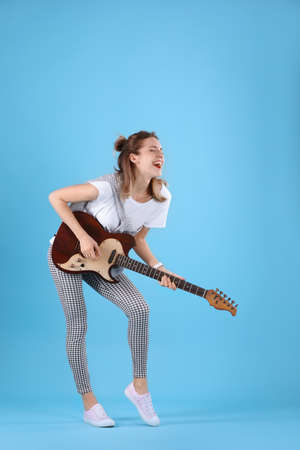 Young woman playing electric guitar on color background