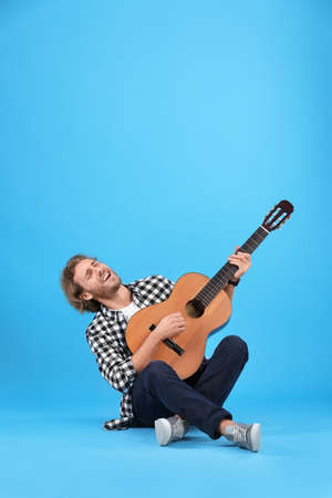 Young man playing acoustic guitar on color background