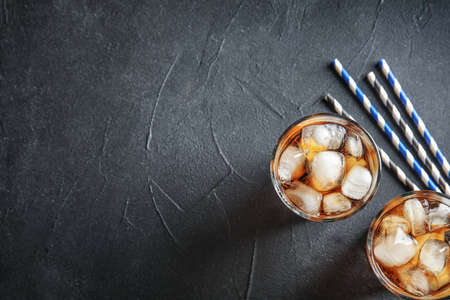 Glasses of refreshing cola with ice cubes on grey background, top view. Space for text Banco de Imagens