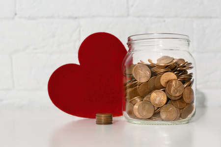 Donation jar with coins and red heart on table. Space for text